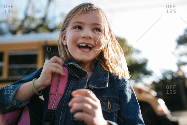 Girl with missing tooth and backpack by a school bus