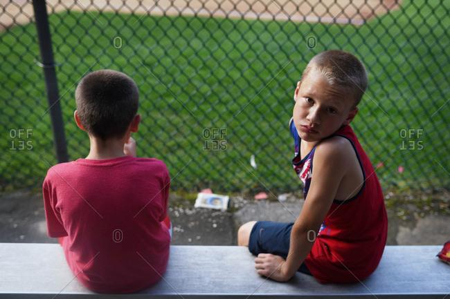 Boys sitting on bench at baseball game