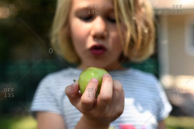 Little girl taking bit of an apple