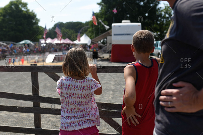 Father and children watching pig races at a fair