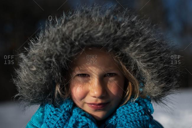 Little girl wearing jacket with furry hood