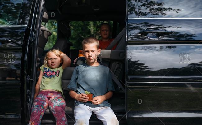 Three kids sitting in a minivan