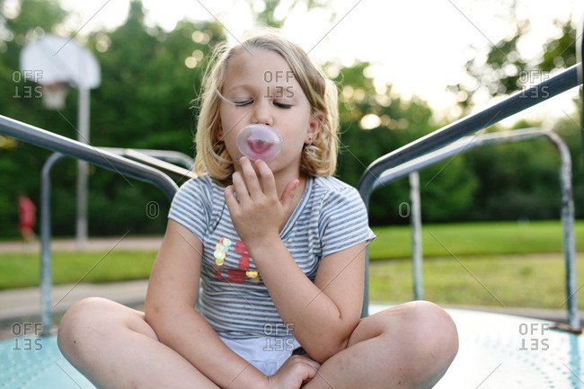 Little girl blowing a bubble on merry go round at a park