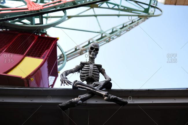 Skeleton toy resting on bar under a ferris wheel