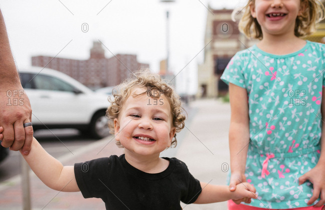 Children holding hands walking on a city street