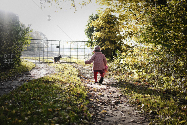 Toddler walking on a path in the sunlight with a doll in her hand