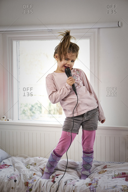 Young girl showing her singing performance in her bedroom