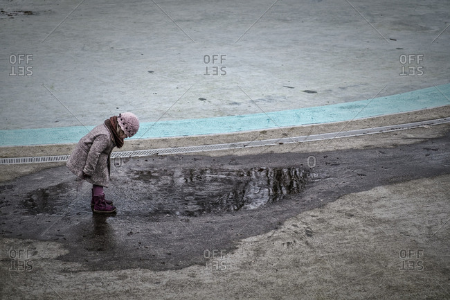 A young girl stands in a puddle on a cold day