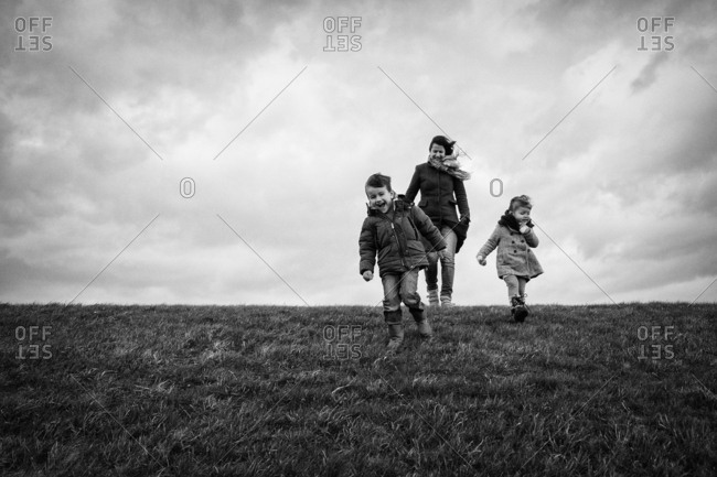 Young family on a dike getting blown away by the wind