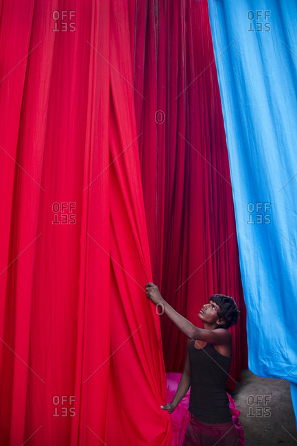 Jaipur, India  - October 4, 2013: Young man working in a cloth dying plant