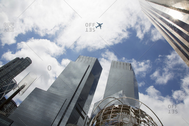 Low angle view of plane flying over the Columbus circle buildings