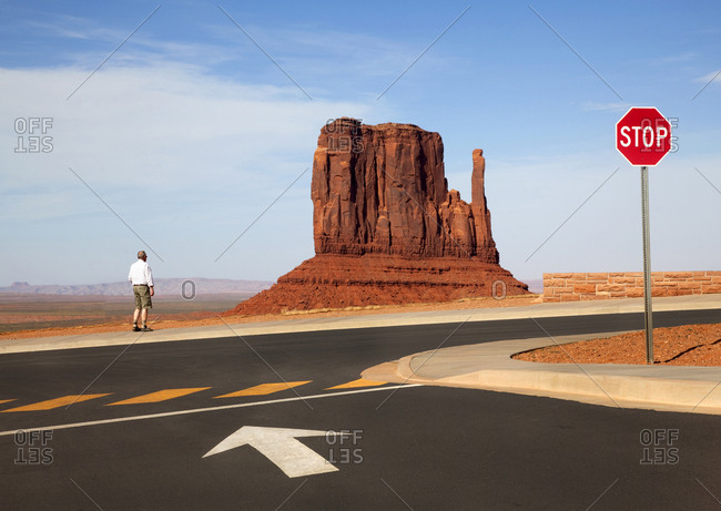 Man looking at red rock in Monument Valley Navajo Tribal Park