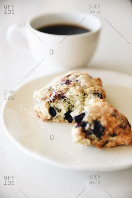 Scones on a white plate and cup of coffee