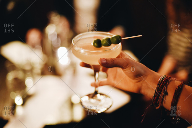 Hand of a woman holding a cocktail garnished with olives