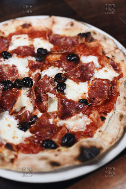 Fresh baked pizza with pepperoni, cheese and black olives