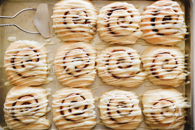 Pastries drizzled with icing on a baking tray