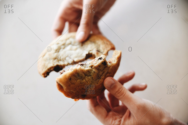 Hands breaking apart a chocolate chip cookie