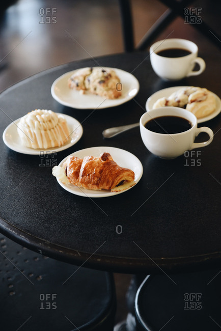 Variety of pastries on plates with coffee on a cafe table