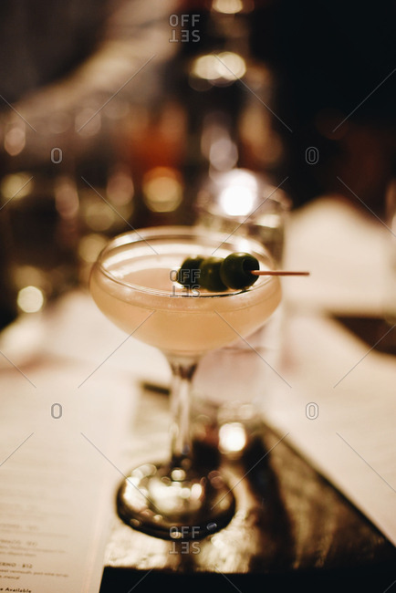 Mixed drink garnished with olives on a restaurant table