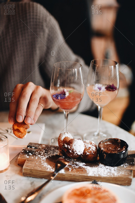 Person at a restaurant table with fried dessert balls and glasses of wine