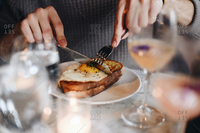Person cutting a piece of toast with a fried egg at a restaurant table