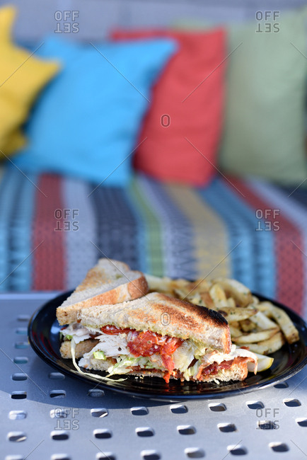 Club sandwich and fries on a plate on an outdoor table