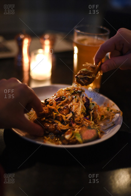 Person eating food from a plate with their hands at a restaurant