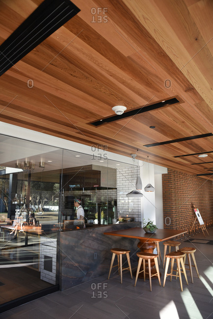 Seating outside of a cafe with natural wood ceilings and large glass windows