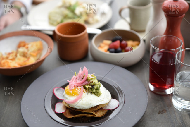Guacamole and egg on a fried tortilla on a breakfast table