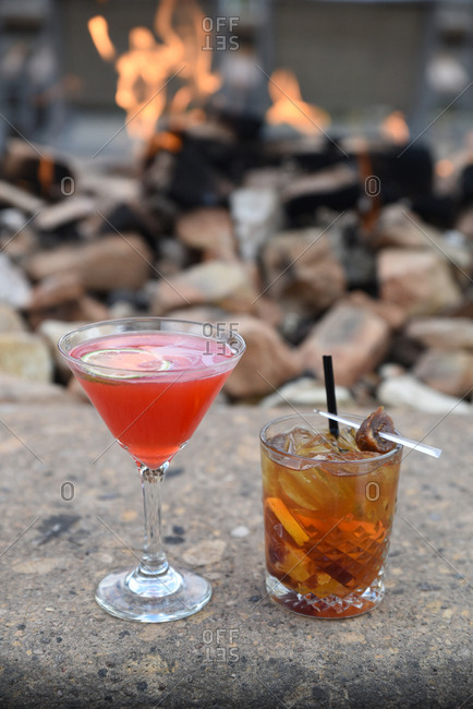Mixed drinks on a stone ledge near a fire pit