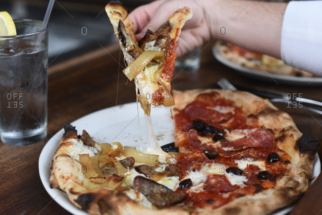 Hand of a person eating a slice of pizza
