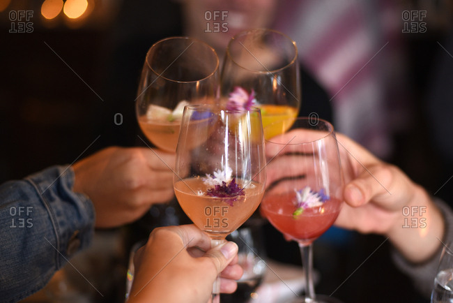 Hands of four friends toasting each other with wine glasses