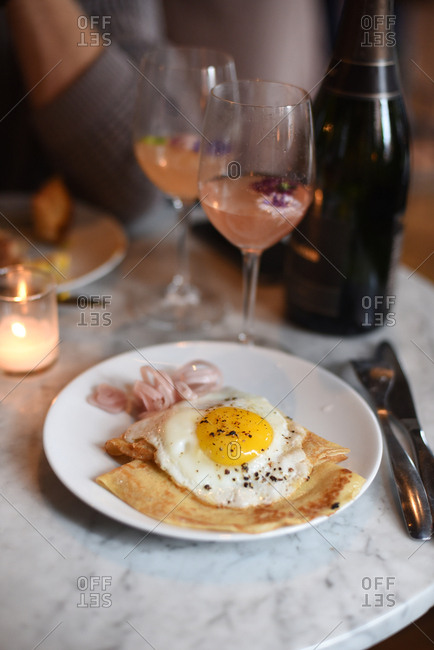 Fried egg and tortillas with wine glasses on a table