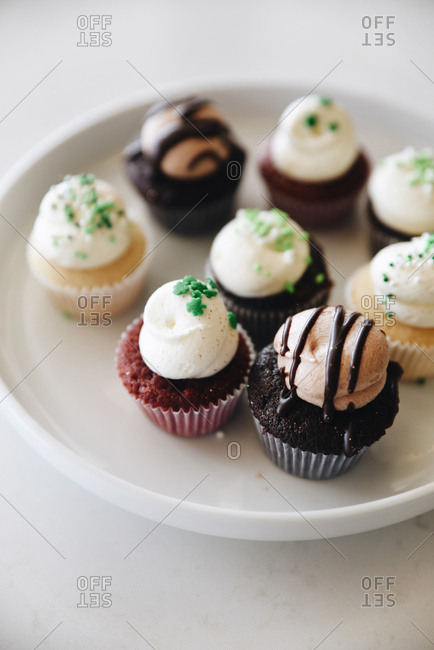 Variety of cupcakes on a platter sprinkled with green sprinkles