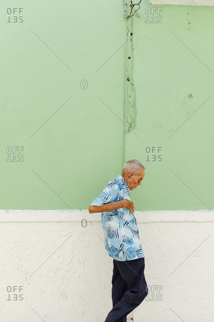 Cartagena, Colombia - March 3, 2017: Old man walking the street beside a green wall in the walled city