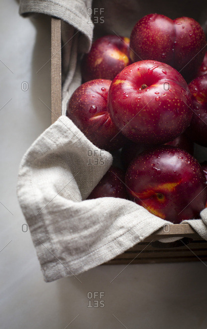 Red plums in a wooden crate