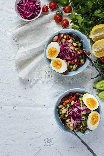 Turkish tangy bean salad known as piyaz served in bowls with halved hard-boiled eggs on the top accompanied by sumac, red onions, peppers, green onions, cucumber, lemon wedges and herbs photographed from top view.