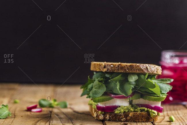 A springtime feta sandwich with avocado, pickled red onions and herbs like arugula, purslane and fresh mint served on a wooden board photographed from front view and a jar of pickled red onions accompanies on the background.