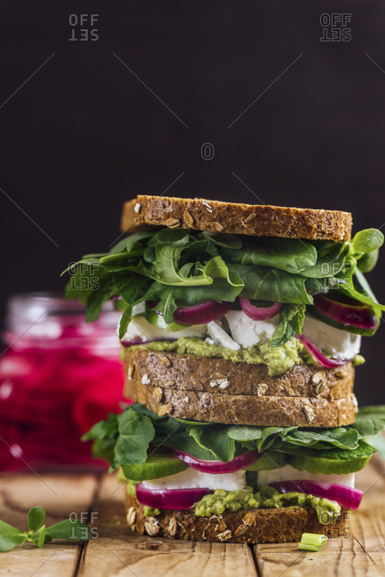 A stack of springtime feta sandwiches with avocado, pickled red onions and herbs like arugula, purslane and fresh mint served on a wooden board photographed from front view and a jar of pickled red onions accompanies on the background.