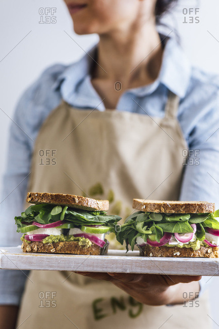 A woman with a blue shirt and a beige apron holding springtime feta sandwiches with herbs, avocado and pickled red onions on a white board photographed from front view.