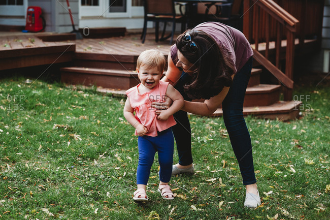 Little girl on a lawn laughing while her mother tickles her