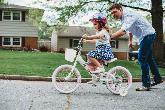 Father helping his daughter learn to ride a bicycle