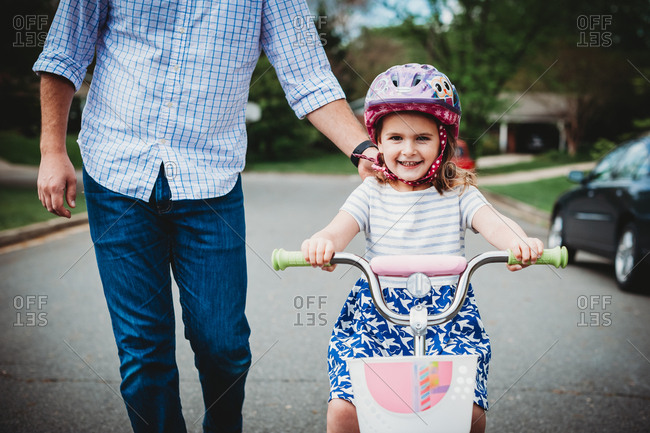 Father holding his daughter's shoulder as she learns to ride a bike