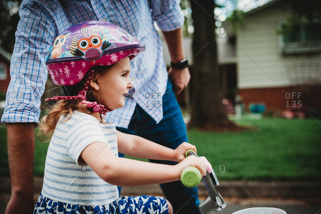 Little girl learning to ride a bike while her father helps