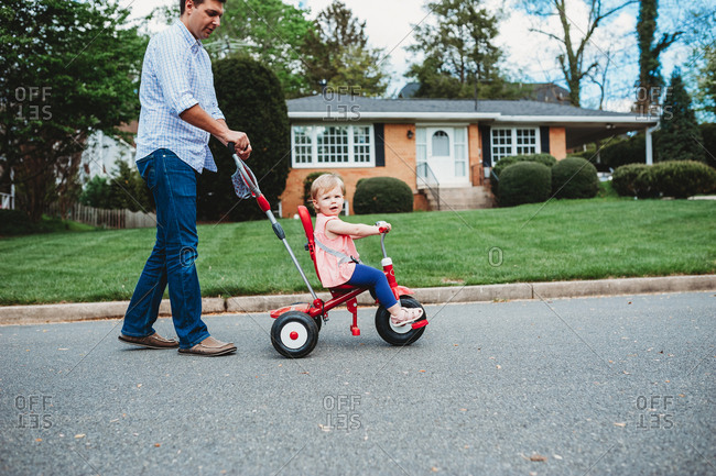 Father pushing his daughter on a red tricycle