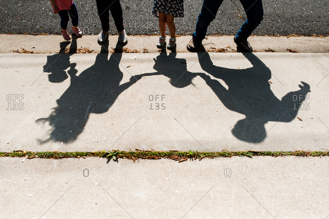 Shadows of a family playing and dancing together outside