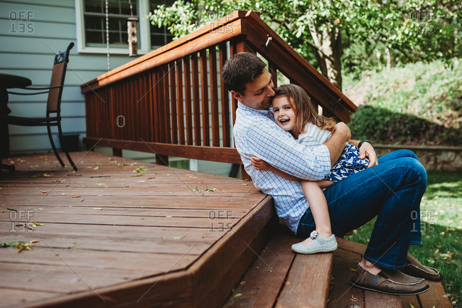 Father and daughter sitting on the steps of a deck hugging and smiling