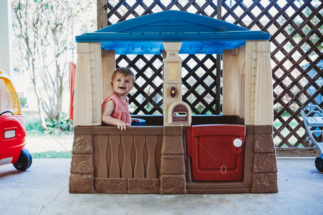 Toddler girl standing in a playhouse smiling
