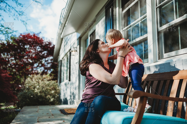 Mother sitting on a bench holding and kissing her toddler daughter