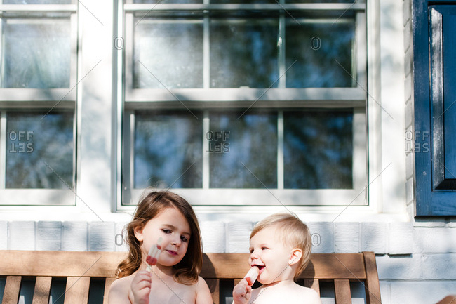 Two sisters sitting on a wooden bench eating frozen popsicles